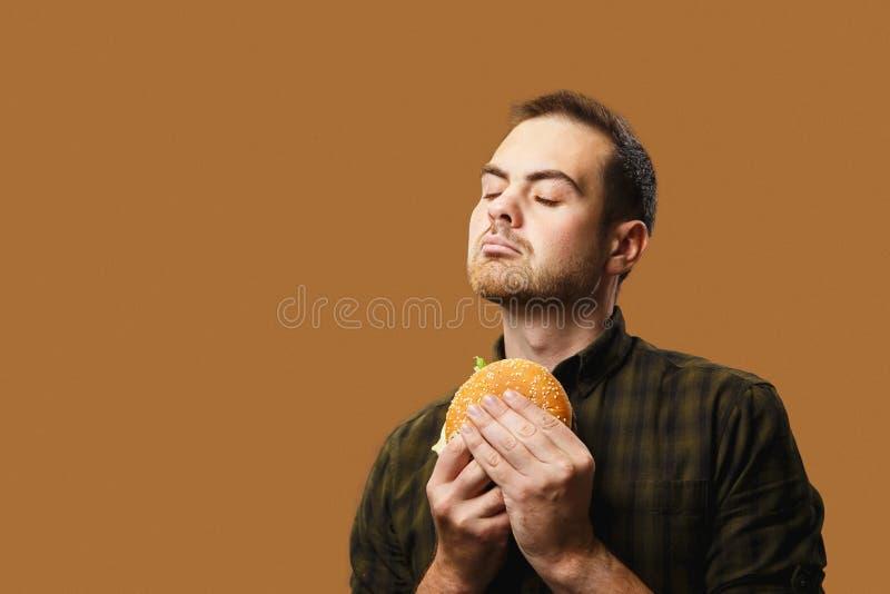 Een jongeman houdt een grote hamburger met eetlust Oranje gekleurde achtergrond, kopieerruimte stock foto's
