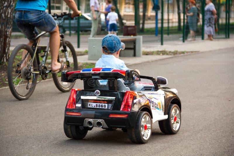 Een jongen berijdt een stuk speelgoed auto in het Park royalty-vrije stock foto's