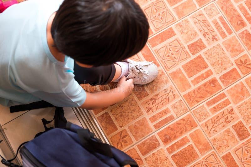Een jongen bindt de schoenveters voorbereidingen treffen om naar school in m te gaan stock afbeelding