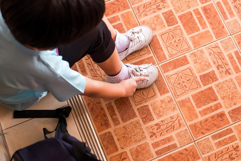 Een jongen bindt de schoenveters voorbereidingen treffen om naar school in m te gaan royalty-vrije stock foto