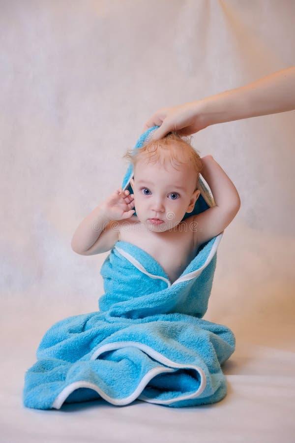 Een jongen in een blauwe handdoekzitting op een lichte achtergrond na een bad Pasgeboren baby die binnen na bad of douche rusten stock foto