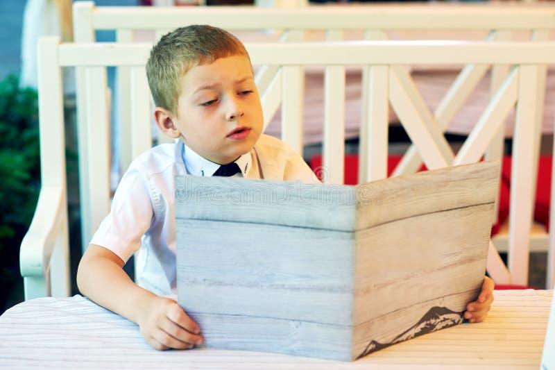 Een jongen in een de zomerkoffie die een menu in zijn handen houden royalty-vrije stock afbeelding