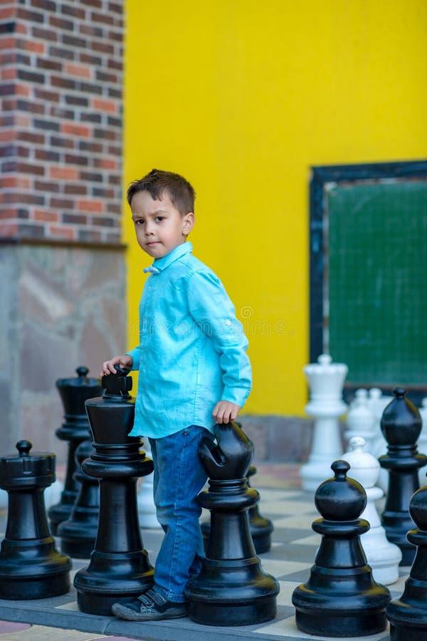 Een jongen die blauwe overhemd en jeansspelen met groot schaak op de speelplaats dragen royalty-vrije stock fotografie