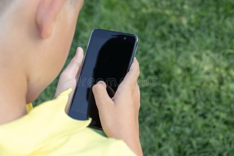 Een jongen, die een celtelefoon, smartphone met het zwarte scherm, groen gras op achtergrond houden royalty-vrije stock fotografie