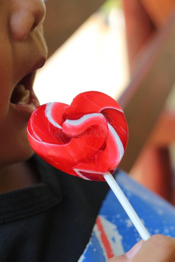 Een jongen die de harten van suikergoedvalentijnskaarten eten stock foto's
