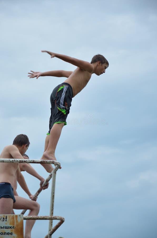 Een jongen die in het water springen stock afbeeldingen