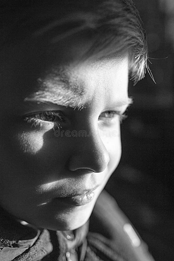 Een jongen die met helft-aangestoken gezicht aan de camera kijken Jongens` s gezicht in het zonsonderganglicht royalty-vrije stock afbeeldingen