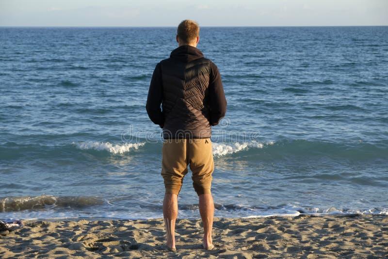 Een jongen die panorama over de overzeese horizon in het strand - wintertijd zonsondergang bekijken royalty-vrije stock foto's