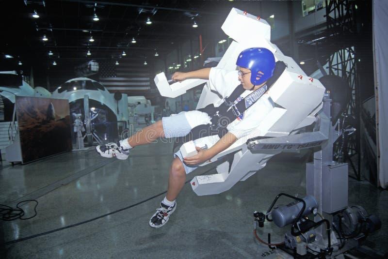 Een jongen die ruimtekamp bijwonen in George C Marshall Space Flight Center in Huntsville, Alabama, probeert een Trainer 1-g van  royalty-vrije stock afbeeldingen