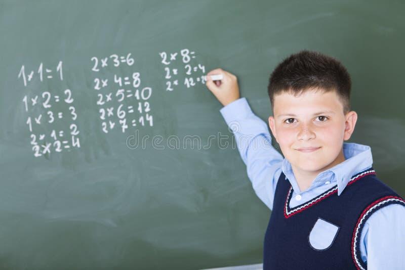 Een jongen doet vermenigvuldiging op bord royalty-vrije stock fotografie