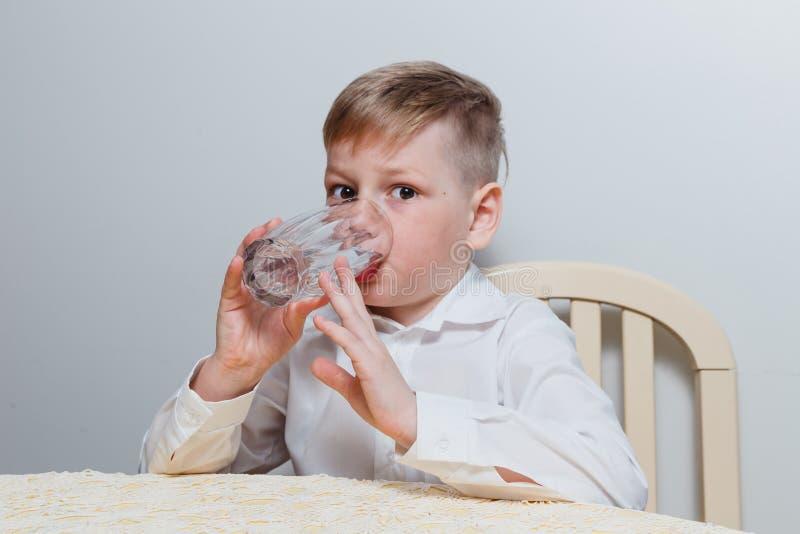 Een jongen drinkt water van een glaskop royalty-vrije stock fotografie