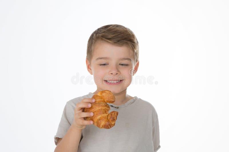 Een jongen en een croissant stock afbeelding