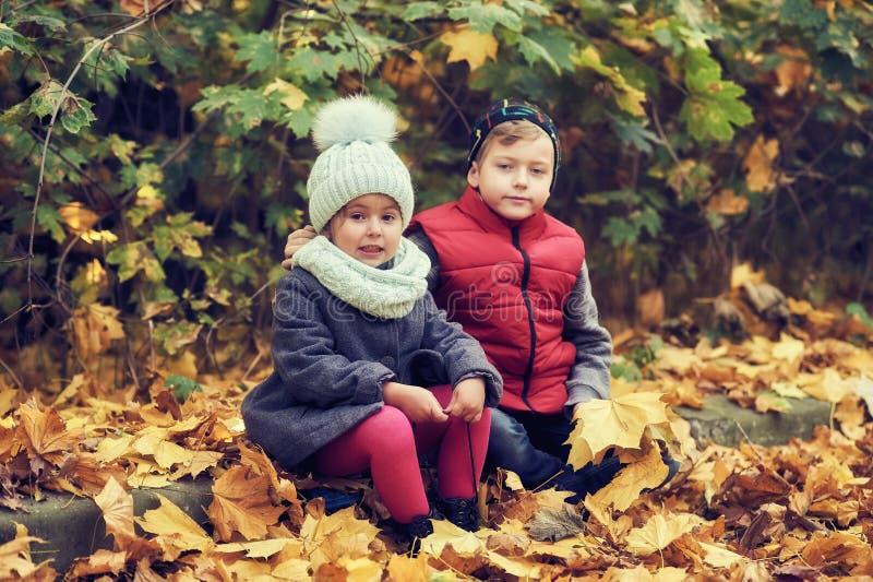 Een jongen en een klein meisje op een de herfstdag voor een gang stock afbeeldingen