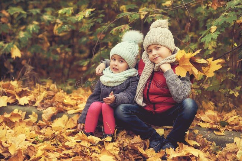 Een jongen en een klein meisje op een de herfstdag voor een gang stock fotografie