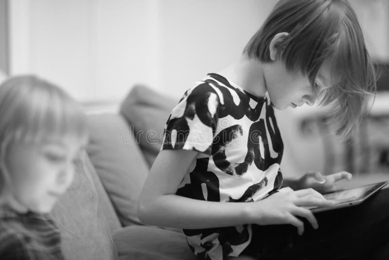 Een jongen en een meisje die een computerspel spelen stock foto