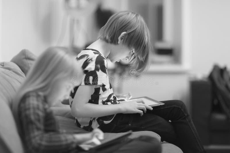 Een jongen en een meisje die een computerspel spelen stock fotografie