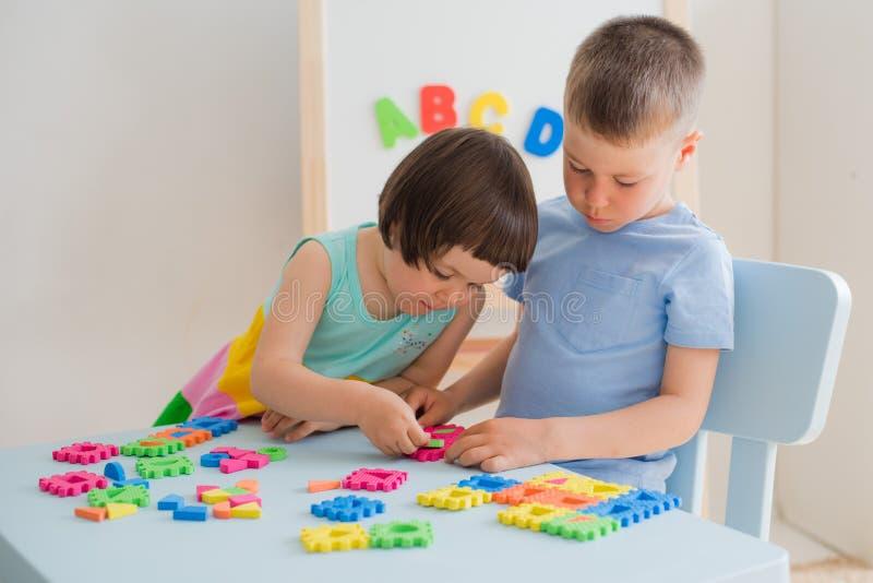 Een jongen en een meisje verzamelen een zacht raadsel bij de lijst De broer en de zuster hebben pret het spelen samen in de ruimt royalty-vrije stock afbeelding