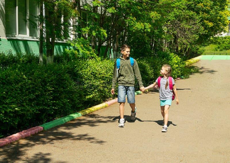 Een jongen en een een meisjesbroer en zuster gaan naar school met schooltassen Horizontaal kader Selectieve nadruk De ruimte van  royalty-vrije stock fotografie
