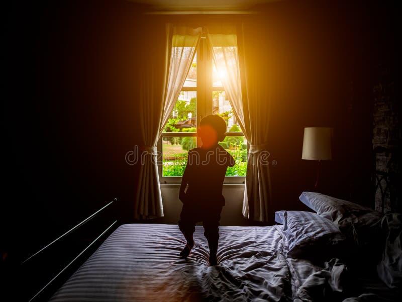 Een jongen heeft pret op de gloed van de het vensterverlichting van het bedsilhouet stock foto