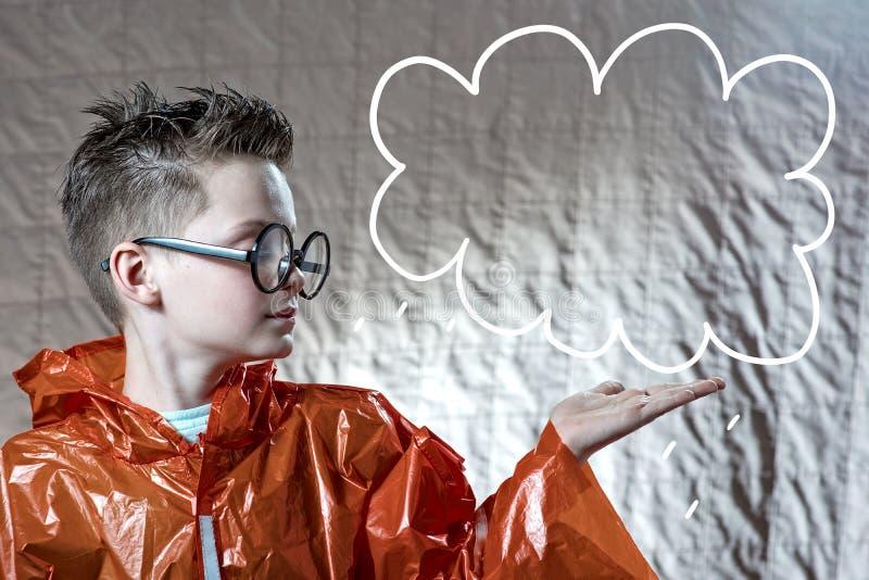 Een jongen in een heldere oranje regenjas en ronde glazen op zijn palm die een geschilderde wolk houden stock foto's