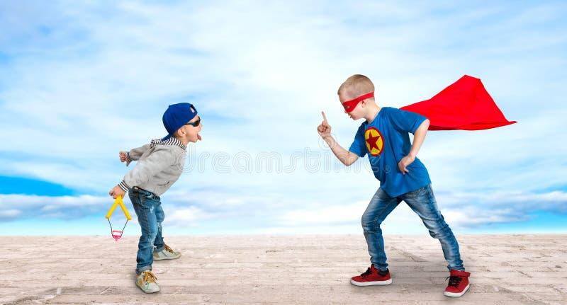 Een jongen in het kostuum van een superhero, onderwijst een weinig intimideert aan de regels van goede behavio stock afbeeldingen