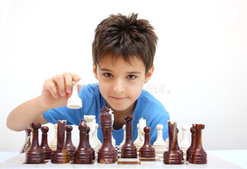 Een jongen het spelen schaak stock afbeeldingen