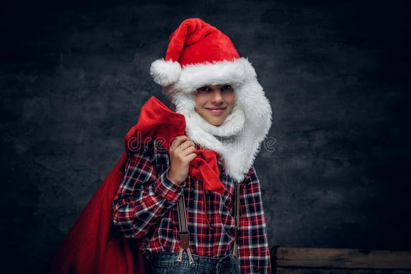 Een jongen in Kerstman` s hoed houdt de zak van de Nieuwjaargift stock foto