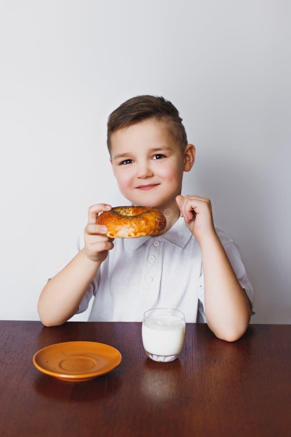 Een jongen, een keuken, een ongezuurd broodje en een melk Gezond Ontbijt stock foto's