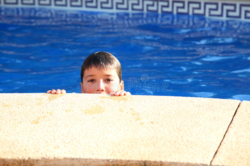 Een jongen kijkt uit een zwembad royalty-vrije stock afbeeldingen