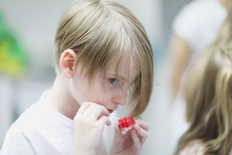 Een jongen mengt een rood tand-schoonmakend gel stock foto's