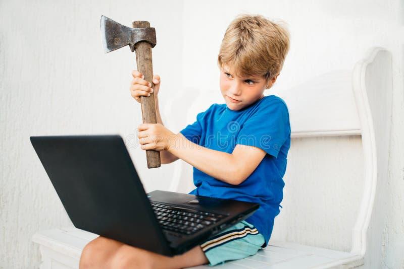 Een jongen met een bijl en laptop stock afbeelding