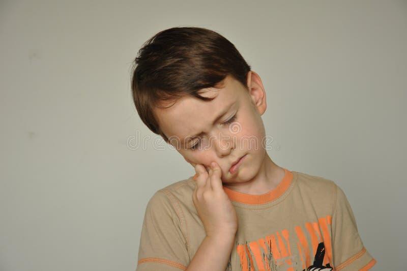 Een jongen met een tandpijn stock fotografie