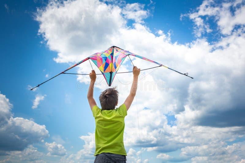 Een jongen met een kleurrijke vlieger in zijn handen tegen de blauwe hemel met wolken Conceptuele fotografie stock afbeeldingen