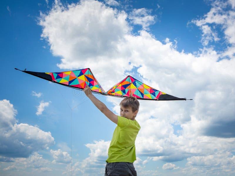 Een jongen met een kleurrijke vlieger in zijn handen tegen de blauwe hemel met wolken Conceptuele fotografie royalty-vrije stock afbeelding