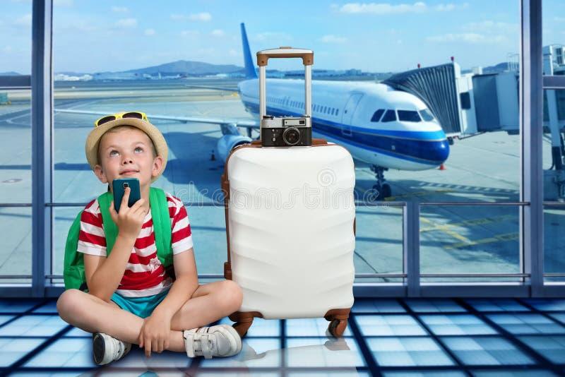 Een jongen met een koffer zit bij de luchthaven en wacht op het landen op het vliegtuig stock foto's