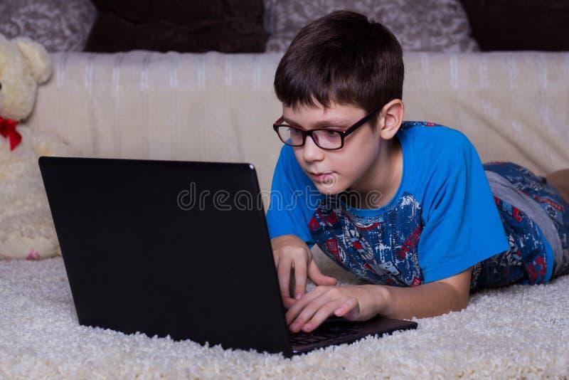 Een jongen met laptop die op de vloer, op het tapijt thuis liggen Technologie, Internet, modern communicatie concept royalty-vrije stock foto