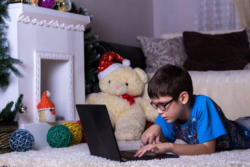 Een jongen met laptop die op de vloer, op het tapijt thuis liggen Technologie, Internet, modern communicatie concept, Nieuwjaar e royalty-vrije stock foto's