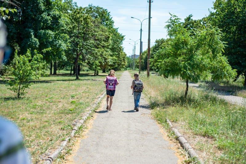 Een jongen met een meisje gaat naar het park naar school, houdend rugzakken met handboeken achter zijn rug royalty-vrije stock afbeeldingen