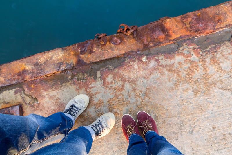 Een jongen met een meisje in jeans en keds bevindt zich op een roestige pijler stock afbeelding