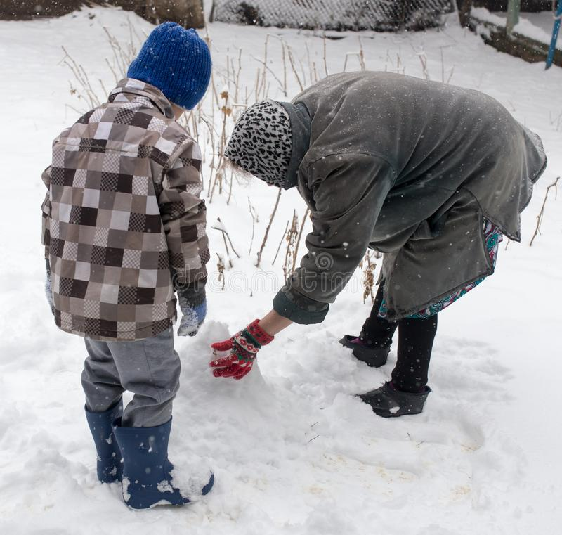 Een jongen met zijn grootmoeder die in de sneeuw spelen royalty-vrije stock afbeelding