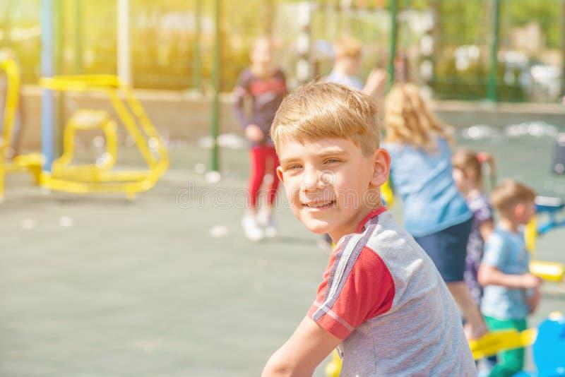 Een jongen op de speelplaats, een portret van een kind tegen de achtergrond van de schommeling van kinderen en vermaak royalty-vrije stock afbeelding