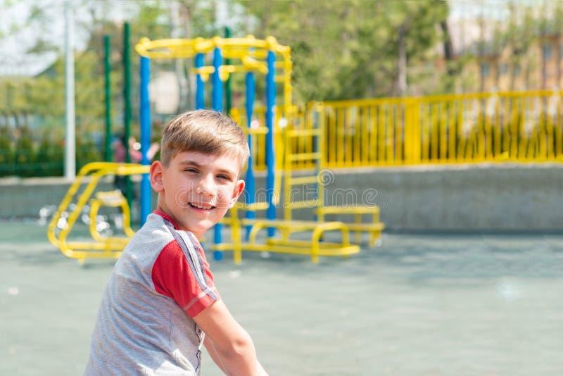 Een jongen op de speelplaats, een portret van een kind tegen de achtergrond van de schommeling van kinderen en vermaak royalty-vrije stock afbeeldingen