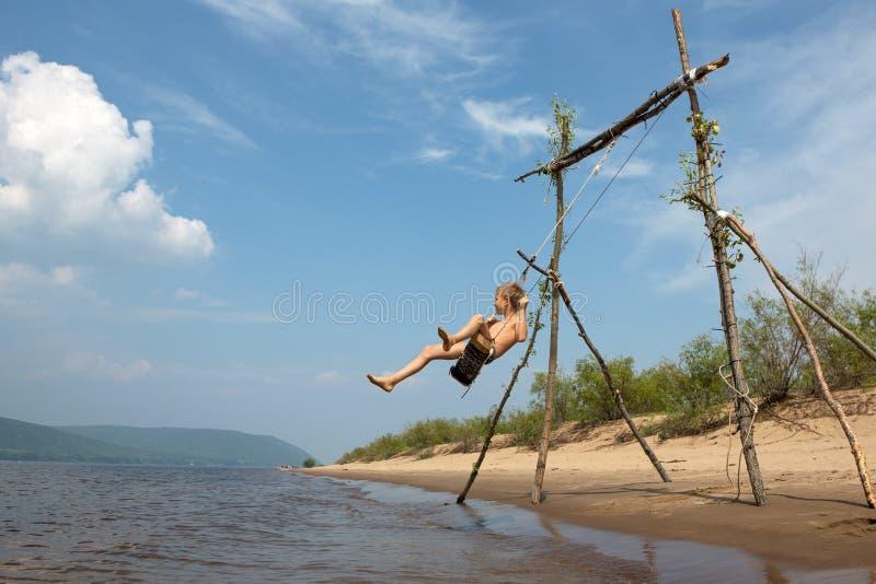 Een jongen op het strand die op een schommeling slingeren De zonnige dag van de zomer stock foto's