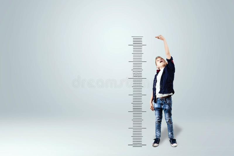 Een jongen op een witte achtergrond toont hoe hij, dromen van het worden een volwassene groeide Het concept de grote groei, zaken royalty-vrije stock afbeeldingen