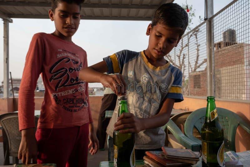 Een jongen opent een bier bij een dakrestaurant in Agra royalty-vrije stock afbeelding