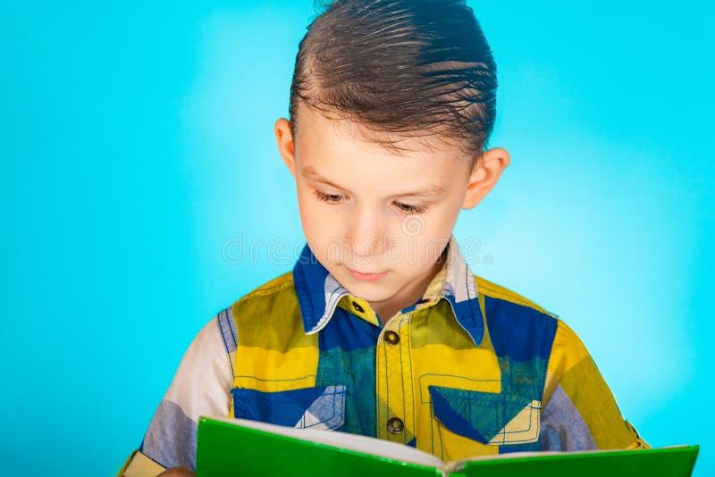 Een jongen in een plaidoverhemd die een boek op een blauwe achtergrond lezen stock foto