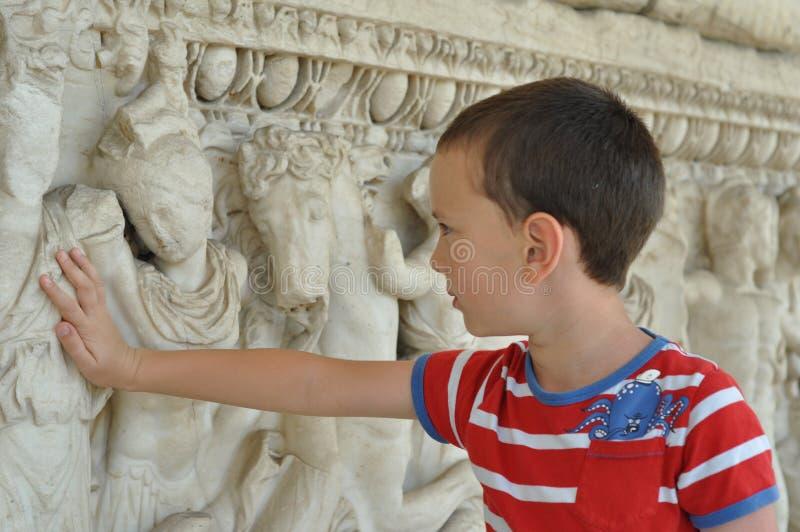 Een jongen raakt historisch monument stock foto's