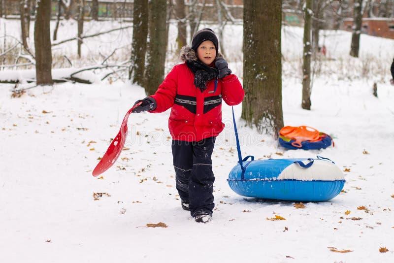 Een jongen in een rood jasje neer op een slee met een sneeuwdia stock foto's