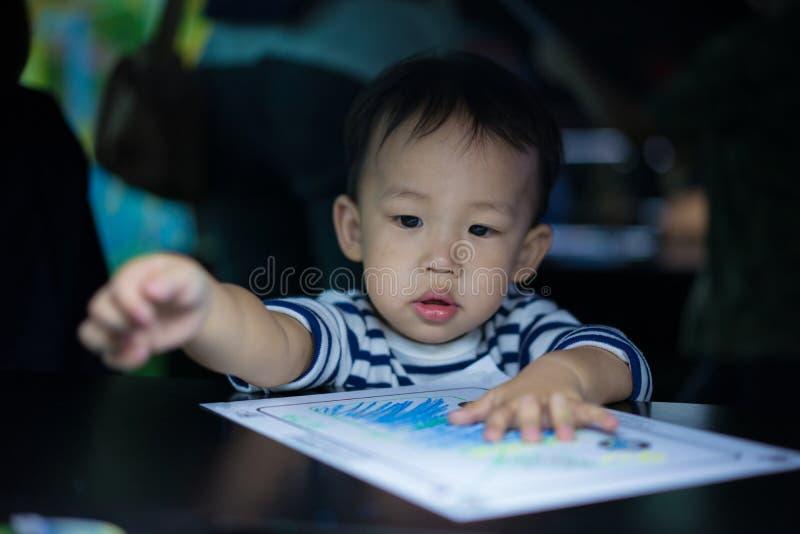 Een jongen schildert met zijn mamma stock fotografie