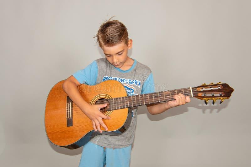 Een jongen speelt de gitaar op een grijze achtergrond in de studio, de brede foto van het hoekclose-up royalty-vrije stock afbeeldingen